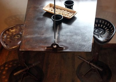 custom-crafted-steel-hung-table-with-adjustable-iron-tractor-seat-stools